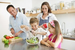 Happy couple with kids (8-11) preparing food together in kitchen